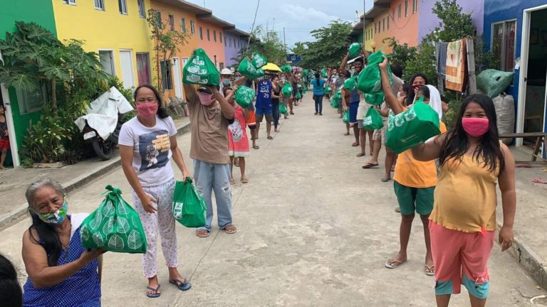 Families from the SM Cares Village in Concepcion, IloIlo are all smiles after receiving their food packs from SM Foundation, Inc.