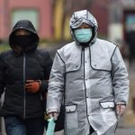 People wear protective facemasks as they walk by a hospital in Wuhan on Jan 26, 2020.PHOTO: AFP
